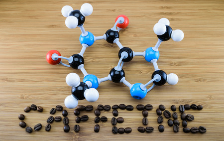 caffeine molecule structure (atomic model) with coffee bean align ìn word on wood background photo