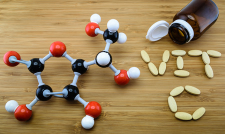 Molecule structure of Vitamin C with a bottle of vitamin C tablet on wood background