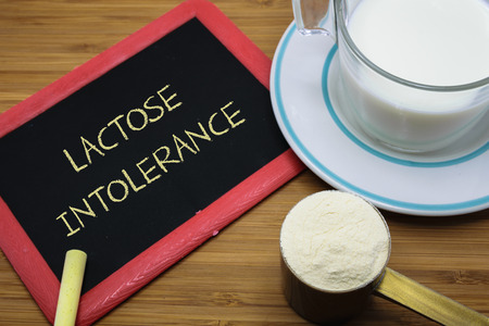 Lactose intolerance word on chalk board with a cup of milk and  milk powder