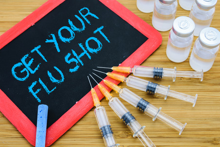 Reminder to Get Your Flu shot written on chalkboard with vaccine in syringes and vials