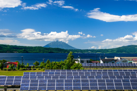 Solarzellenplatte und Dorf in ländlicher Umgebung mit Berglandschaft Hintergrund Standard-Bild
