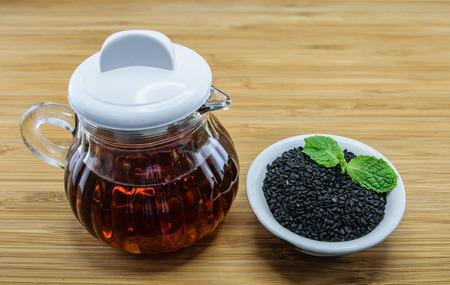 ajonjoli: aceite de sésamo en semillas jarra de vidrio y de sésamo negro en un tazón en el fondo de madera