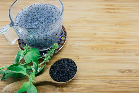 basil: Gelatinous basil seeds in a cup and basil leaves and seed on wood background