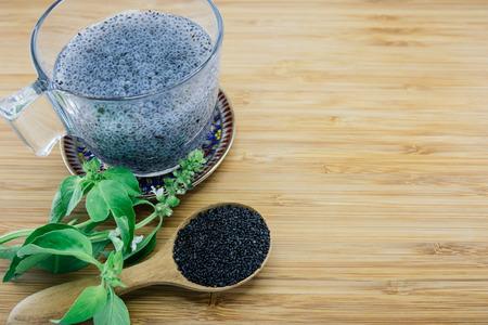 basilio: Semillas de albahaca gelatinosas en una taza y hojas de albahaca y semillas en el fondo de madera Foto de archivo