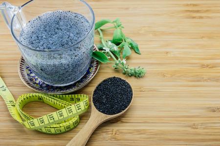 albahaca: Semillas de albahaca gelatinosas en una taza y hojas de albahaca y semillas y cinta de medición en el fondo de madera Foto de archivo