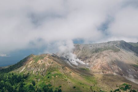 erupt: View of Mount Usu summit and fuming volcanic smoke located at the south of lake toya, hokkaido, japan Stock Photo