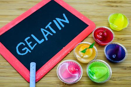 gelatina: Gelatina escrito en la pizarra con postres de gelatina en el fondo de madera Foto de archivo