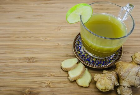 fresh ginger: A cup of fresh ginger drink with fresh ginger root on wood background Stock Photo