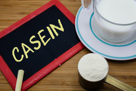 casein: Casein written on chalkboard with a cup of milk and a scoop of milk powder on wood background