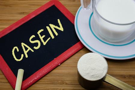 casein: La case�na escrito en la pizarra con una taza de leche y una cucharada de leche en polvo en el fondo de madera
