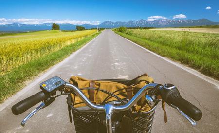 北海道美瑛パッチワークの道、夏のヒルズ、麦畑をサイクリングします。バイカーの目からを表示します。