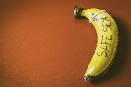 safe sex: Safe sex concept of condom on banana with red background