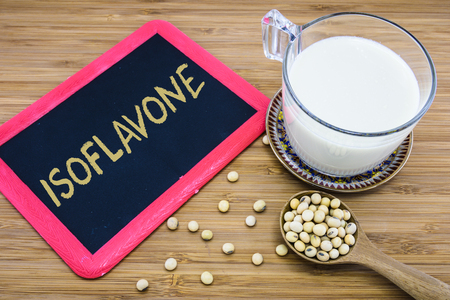 leche de soya: Isoflavonas escrito en la pizarra con una taza de leche de soja y la soja sobre fondo de madera Foto de archivo