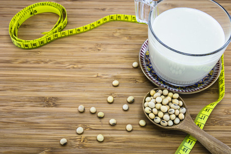 soymilk: A cup of soymilk with soybean and measuring tape on wood background for concept of weight control