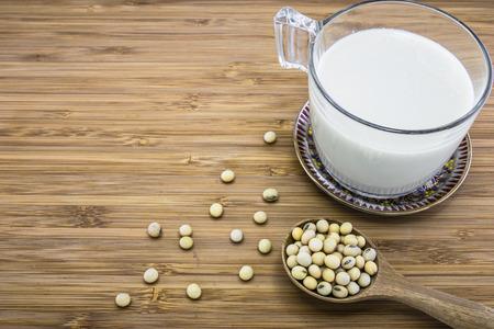 leche de soya: Una taza de leche de soja con soja y en el fondo de madera