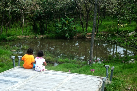 Twin young girls relaxing by look to the pond  photo