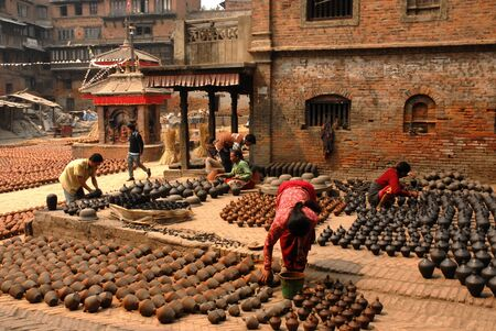 Woman arranging pots outside a pottery shop in the ancient town of Bhaktapur Nepal   Stock Photo - 15724130