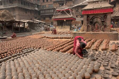 Woman arranging pots outside a pottery shop in the ancient town of Bhaktapur Nepal   Stock Photo - 15724144
