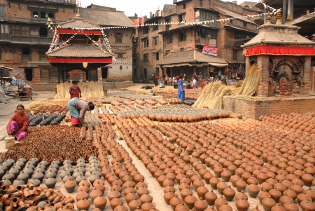 Woman arranging pots outside a pottery shop in the ancient town of Bhaktapur Nepal