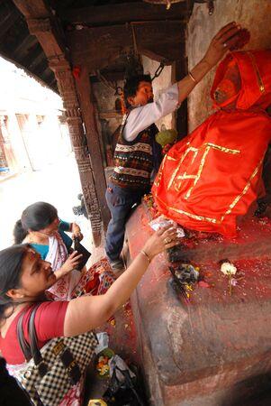 terrifying: Standing woman is praying to the terrifying Hindu Goddess Hanuman in a street of Kathmandu, Nepal