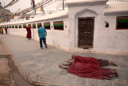 KATHMANDU,NEPAL- MARCH 15  Tibetan pilgrim circles the holy Boudhanath stupa on March 15, 2012 in Kathmandu, Nepal  Here a devotee performs full body prostration for an entire day