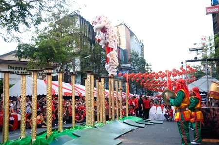 going for it: BANGKOK- THAILAND-JANUARY 24  Chinese Lion jumping on the Mei flower poles in Chinese New Year Festival on January 24, 2012 in Bangkok  It hesitates for further jumping or going back