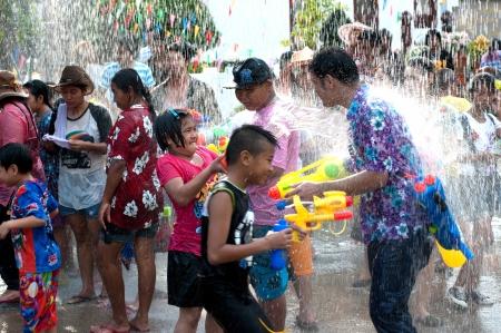 personas festejando: Ayuttaya, Tailandia, 13 de abril Personas no identificadas celebrando Songkran tailand�s nueva fiesta del agua a�o hijo y su pistola de agua en la carretera 13 de abril 2012 en Ayuttaya, Tailandia Editorial