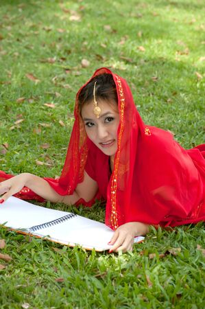 Pretty Asian woman in red Indian clothes lying read a book  photo