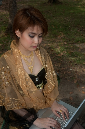 Pretty Asian woman in black Indian clothes working with Laptop   photo