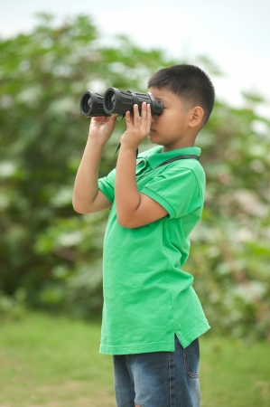 Young Boy looking into binocular  photo