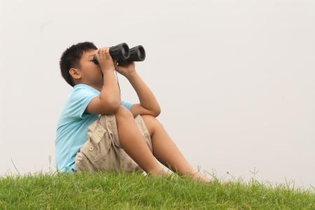 Young Boy looking into binocular