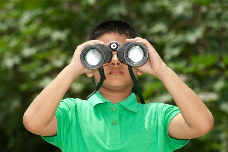 Young Boy looking into binocular  photo