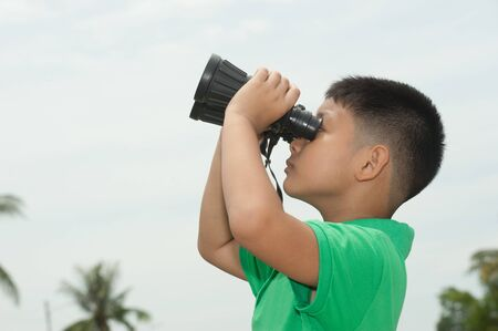 Little boy looking through the binocular  photo
