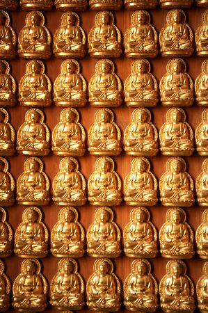 Little golden buddha on the wall background