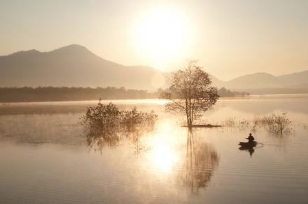 Fisherman on big lake in morning