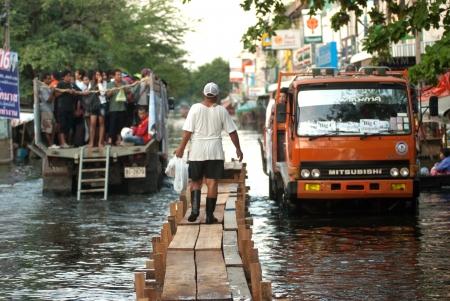 BANGKOK - NOVEMBER 30   Villagers going home on the trucks and wood bridge during the flooding of November 30, 2 011 in Bangkok, Thailand   Stock Photo - 16680390