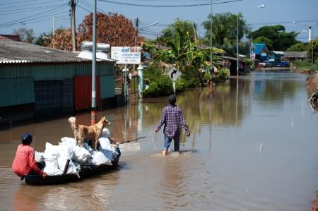 AYUTTAYA,THAILAND - NOVEMBER 13  People floating their belongings while wading through deep water during the monsoon flooding of November 13, 2011 in Ayuttaya, Thailand   Stock Photo - 16704889