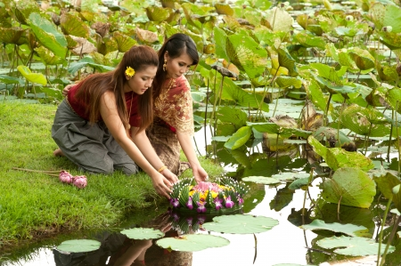 Pretty Thai woman in traditional clothes posing floating flower kratong festival in Thailand Stock Photo - 16790791