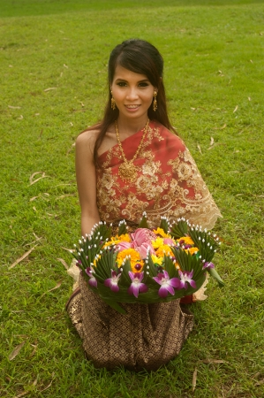 Pretty Thai woman in traditional clothes pose sitting hold flower kratong   photo