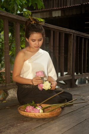 Pretty woman in Thai style clothes in posing artificial flowers Stock Photo - 16790835