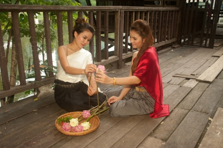 Pretty woman in Thai style clothes in posing artificial flowers Stock Photo - 16790808
