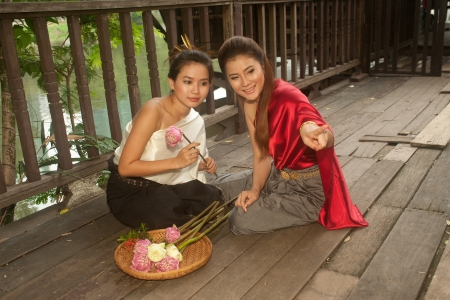 Pretty woman in Thai style clothes in posing artificial flowers   photo