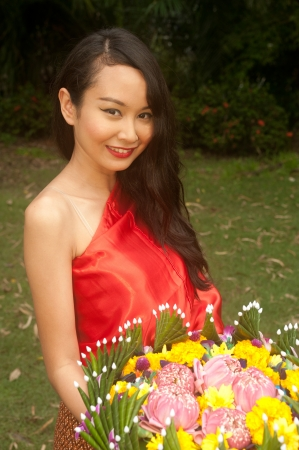 Pretty Thai woman in traditional clothes pose standing hold flower kratong Stock Photo - 16790834