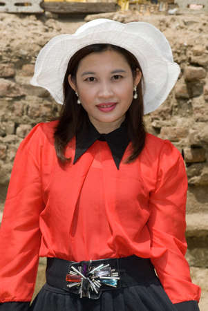 Pretty Asian woman in red dress and white hat   photo