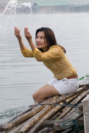 Pretty Asian woman playing water in floating house Stock Photo - 16873694