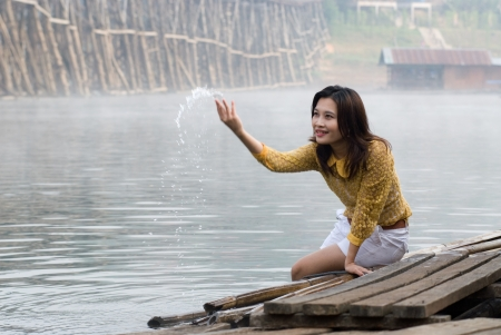 Pretty Asian woman playing water in floating house   photo