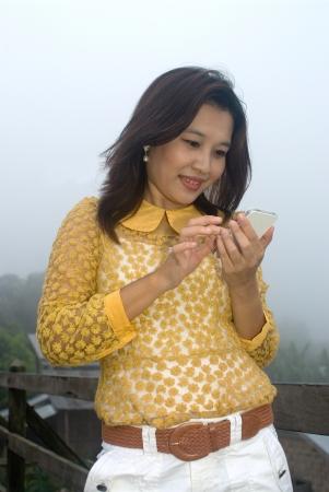 Pretty Thai woman in yellow dress on phone   photo