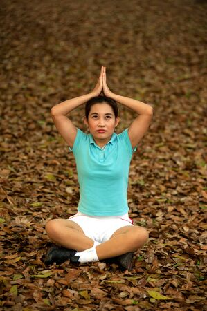 Pretty Asian woman practising Yoga on ground in the park   photo