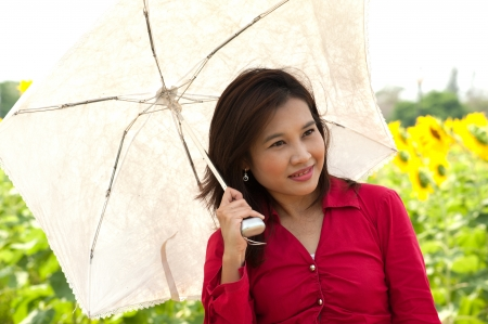 Portrait of pretty Asian woman hold white umbrella posing in sunflower field   photo