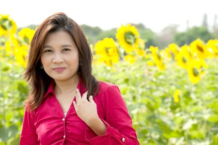Portrait of pretty Asian woman posing in sunflower field   photo